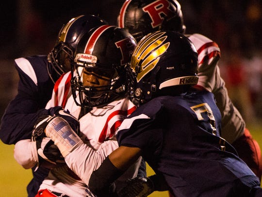 A Rossview player is tackled by 2 Northeast players