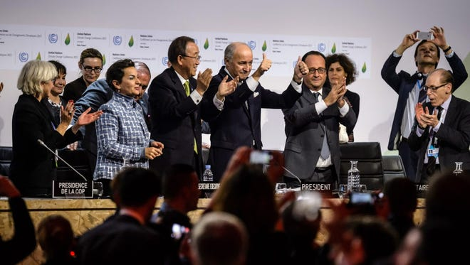 World leaders celebrate the climate accord adoption on Dec. 12, 2015.