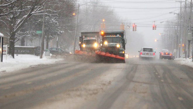 Plows clear roads Monday morning.