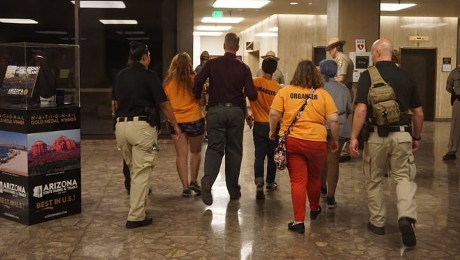 Arizona Department of Public Safety officers take Phoenix March For Our Lives organizers by the arms and lead them out the Arizona Capitol Executive Tower after a six-hour 'die-in' on April 20.