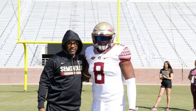 Florida State's newest commit, four-star defensive end Curtis Fann, posing with Willie Taggart.