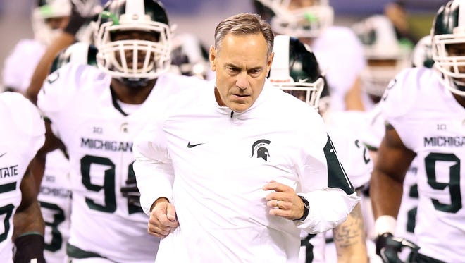 Head coach Mark Dantonio of the Michigan State Spartans leads his team onto the field before the game against the Iowa Hawkeyes in the Big Ten Championship at Lucas Oil Stadium on December 5, 2015 in Indianapolis, Indiana.