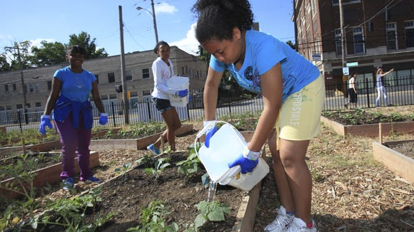 Tiondra Poyntz, 12, right, waters cucumber plants in the Parkland Community Garden at 28th and Dumesnil streets. June 13, 2013