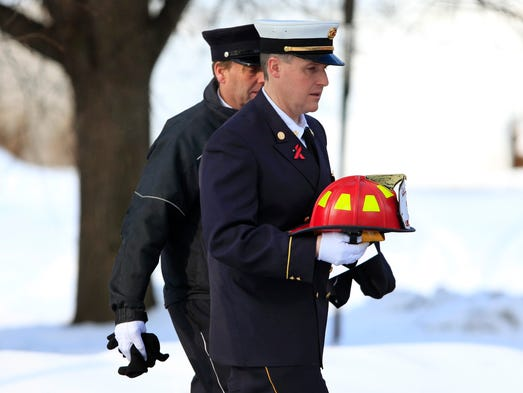 Penfield Fire Department Chief Chris Ebmeyer arrives at the funeral of Tyler Doohan, Lewis J. Beach and Stephen D. Smith. He is carrying the helmet the company had made to honor Tyler.