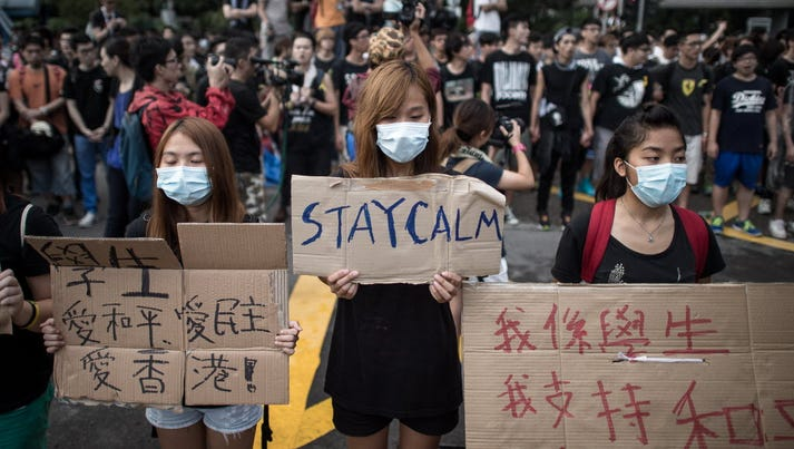 Pro-democracy demonstrators display placards as they gather near a ceremony marking China's 65th National Day in Hong Kong on Oct. 1.