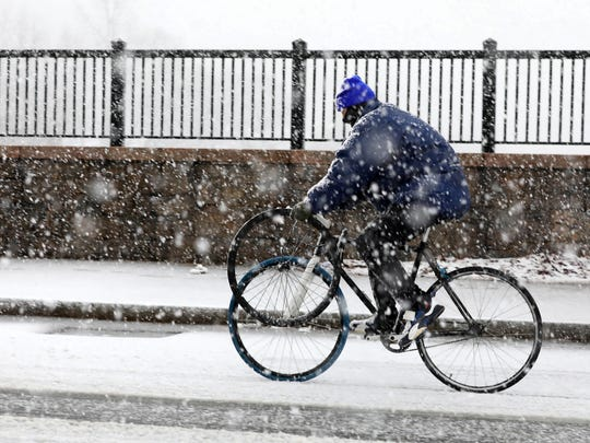 1:13 p.m. A bicyclist makes his way, with tire in hand, along McLean Avenue in Yonkers, as a nor'easter moves into the area, March 7, 2018.