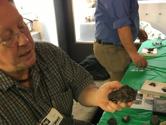 Greg Lemke holds a meteorite from a 1947 Russia meteor.