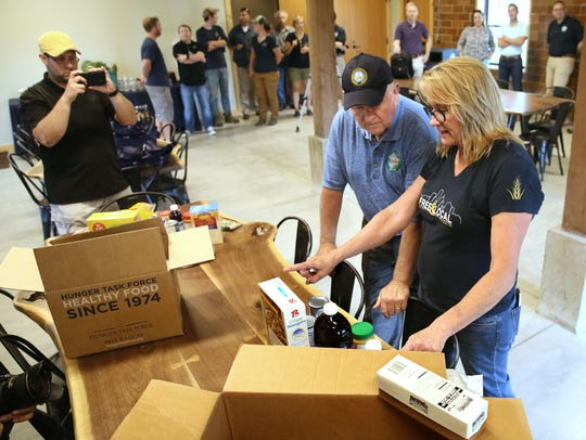 Agriculture Secretary Sonny Perdue tours the Hunger Task Force farm in Franklin in 2017. Here Sherrie Tussler, executive director of Hunger Task Force (right), explains to Perdue how they pack food boxes for families and seniors who utilize some of the U.S.D.A. commodity food.