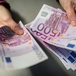 A bank employee holds 5,000 euros in 500-euro notes at a Sparkasse bank in Munich, Germany, Feb. 3, 2016. Germany is considering imposing an upper limit on payments in cash as part of its fight against terrorism and money laundering.