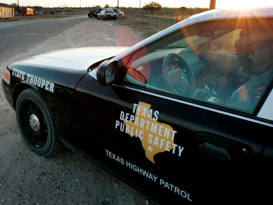 A Texas State Trooper sits in his vehicle in Eldorado,