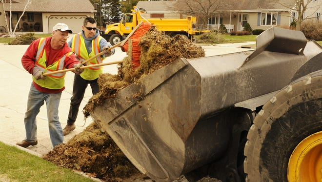 City of Manitowoc Department of Public Works employees, from left, Curtis Larson and Nick Binsfeld use brooms to sweep a lawn and leaf pile into the bucket of the front-end loader operated by Kerry Krajnik (not pictured) as the crew does spring cleanup collection on Dueno Court in Manitowoc in 2011.