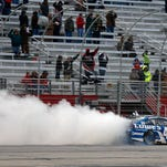 Jimmie Johnson (48) does a celebratory burnout after winning the NASCAR Sprint Cup series auto race at Atlanta Motor Speedway, Sunday.