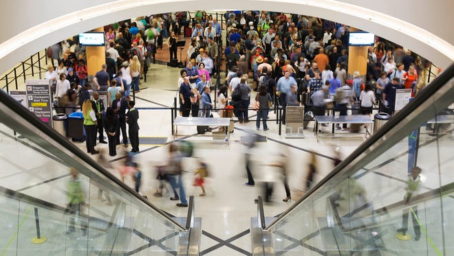 This file photo from May 19, 2016, shows travelers queuing for a security checkpoint line at Hartsfield-Jackson Atlanta International Airport.
