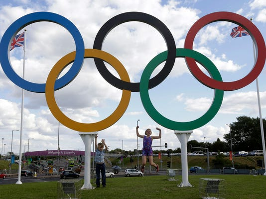FILE - In this July 28, 2012 file photo, British children pose for photos under a sculpture of the Olympics rings, in Coventry, England. Boston, Los Angeles, San Francisco and Washington are the cities still in the running for a possible U.S. bid to host the 2024 Summer Olympics. (AP Photo/Hussein Malla, File)