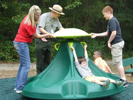 Adults help kids get the new merry-go-round going at