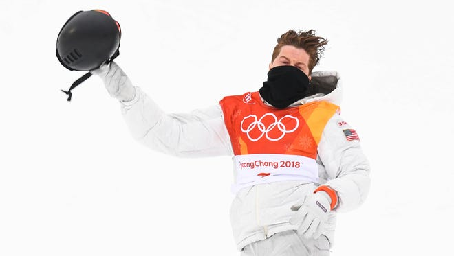 Shaun White gets ready to toss his helmet while celebrating his first run in the men's halfpipe final.
