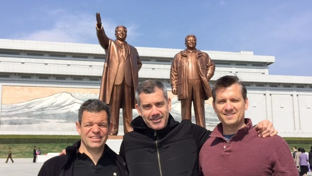 Mark Smerznak, 43, Bruce Aitken, 45, and Mike Keogh, 44, left to right, are American friends who  work for U.S. firms in Beijing. They stand in front of giant statues of North Korea's Kim Il Sung and Kim Jong Il on April 13, 2015, in Pyongyang, after the city marathon a day earlier.