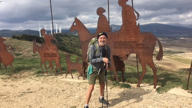 David Larwa in front of a famous monument to Camino pilgrims which overlooks the Arga Valley on Alto del Perdon.