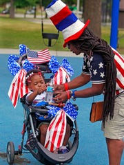 Cookie Taylor gives her granddaughter Gwendolyn Leslie Taylor, 2, water during the Fourth of July celebration in Sherman Park on July 4, 2016.