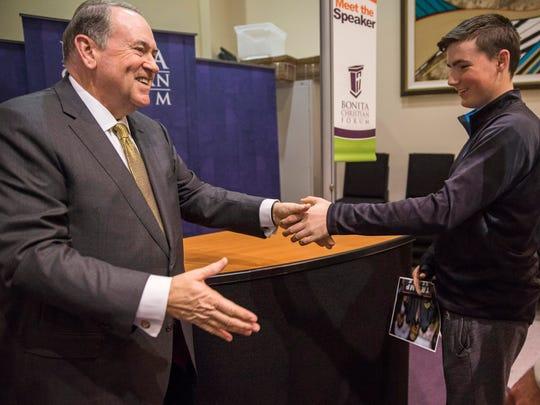 Mike Huckabee, left, shakes hands with John Harley,