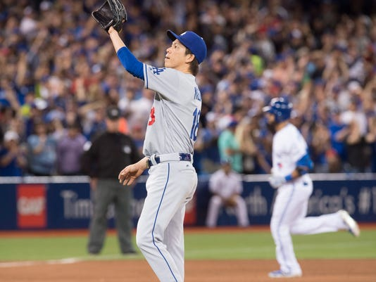 Los Angeles Dodgers starting pitcher Kenta Maeda stands on the mound as Toronto Blue Jays Jose Bautista rounds the bases on his two run homer during sixth inning inter-league action in Toronto on Friday, May 6, 2016.(Frank Gunn/The Canadian Press via AP)