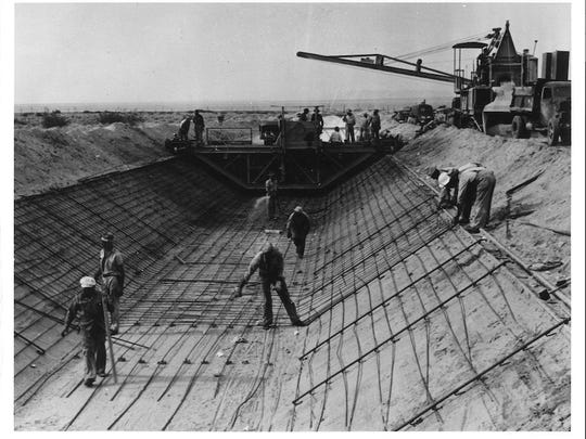 Workers build the Coachella Canal in 1946, placing rebar on cut banks of the wasteway. The Salton Sea can be seen in the distance.