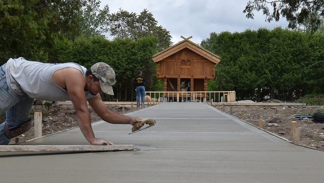 Victor Colosimo of Colosimo Construction of Ellison Bay applies finishing touches to a path leading to a stabbur, the centerpiece of Al Johnson's Swedish Restaurant & Butik's new beer garden. The building with its engraved rosemaling accents was shipped from Norway.