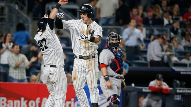 New York Yankees' Austin Romine, left, celebrates with the Tyler Austin after scoring on Austin's seventh-inning, two-run home run off Boston Red Sox starting pitcher David Price in a baseball game in New York, Tuesday, Sept. 27, 2016.