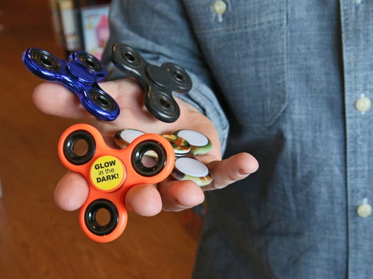 Matthew Poulson, co-owner of Ruckus & Glee in Wauwatosa, has a handful of fidget spinners, the popular children's toy and tool that is also gaining ground with adults.