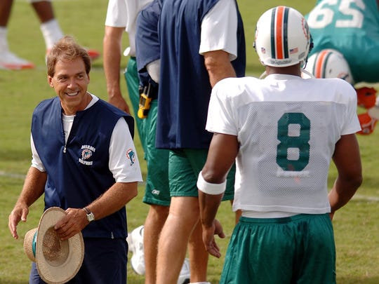 Miami Dolphins head coach Nick Saban, left, smiles at quarterback Daunte Culpepper (8) during summer football camp on July 31, 2006