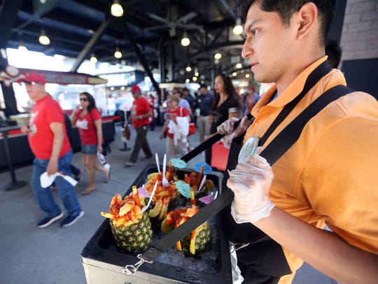 """Jonathan Mesta waited on customers for his """"Piñas Locas"""" along the main concourse at an El Paso Chihuhuas game in April. Concessions are among the jobs available at an upcoming job fair."""