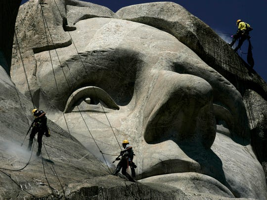 In this July 22, 2005 file photo, German workers Gerhard Buchar, right, and Winfried Hagenau, left, along with National Park Service employee, Darin Oestman, use pressure washers to clean around the face of Thomas Jefferson at Mount Rushmore National Memorial in South Dakota.