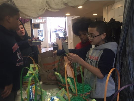 "T.J. Stokes, Josh Wenzel, Michael ""Christopher"" Jenkins and Joe Medina read the instructions ton help them create Easter baskets for kids at the Feeding Hands Pantry at Emmanuel Church in Somerville. The Dunellen kids worked out of Melanie's Hair Salon on North Avenue."
