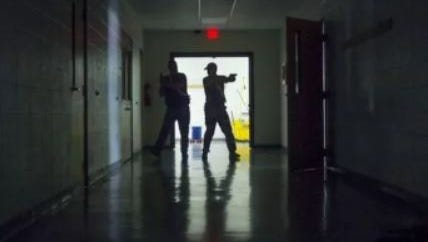 Two Missouri school employees make their way down a darkened hallway, clearing each room as part of their training with Shield Solutions at Fairview School.
