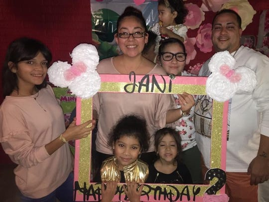 Paola Rios Rosario, left, celebrates her first party in Iowa with her aunt Rosa Rios and uncle Harry Rios, far right, whom she lives with now.
