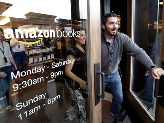 FILE - In this Tuesday, Nov. 3, 2015, file photo, employees smile as they unlock and open the door to the first customers at the opening day for Amazon Books, the first brick-and-mortar retail store for online retail giant Amazon. Although Amazon already dominates e-commerce, 90 percent of worldwide retail spending is still in brick-and-mortar stores, according to eMarketer. Amazon has the chance to change retail with automation and data-mining technologies borrowed from e-commerce.