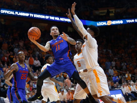 Florida guard Chris Chiozza (11) is defended by Tennessee guard Jordan Bone, right, and forward Admiral Schofield (5) during the second half of an NCAA college basketball game Wednesday, Feb. 21, 2018, in Knoxville, Tenn. (AP Photo/Crystal LoGiudice)