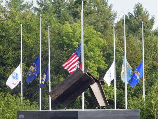 In this Sept. 11, 2013 file photo, flags fly at half-mast