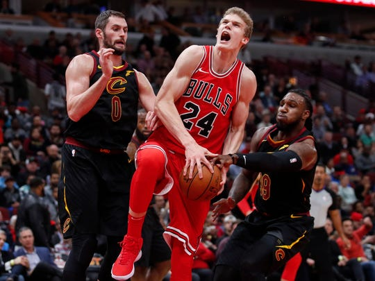 Chicago Bulls forward Lauri Markkanen (24) goes to the basket between Cleveland Cavaliers forward Kevin Love (0) and forward Jae Crowder (99) during the first half at United Center.