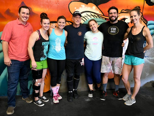 Ken Ogden poses for a photo with some of the coaches at CrossFit OwnIt in West Melbourne.