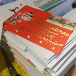"""Santa Claus oversees his team of """"angels,"""" who are opening and responding to letters addressed to Santa Claus in Himmelpfort, Germany."""