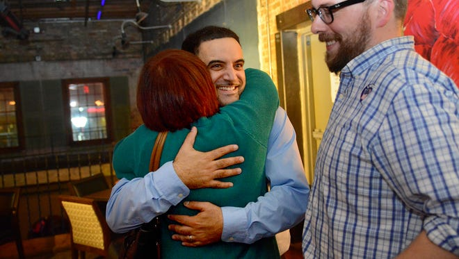 Adam Hussain gets a hug from his mother, and now Lansing City Council colleague, Jody Washington Tuesday, November 3, 2015, at The Exchange in downtown Lansing after beating incumbent A'Lynne Boles for a seat on the council. Hussain's campaign manager Thomas Morgan looks on a smiles.