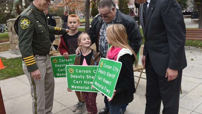 Carson City Sheriff Ken Furlong, left, Kevin Howell, center, and Governor Brain Sandoval gather around Deputy Carl Howell's children Jayden Howell, 11, left, Annalise Howell, 7, center, and Lillian Howell, 9, who where given replicas of the Deputy Sheriff Carl Howell Memorial Freeway Memorial Freeway sign during the dedication ceremony of the Carson City Deputy Sheriff Carl Howell Memorial Freeway on the capitol grounds on Tuesday Dec. 8, 2015.