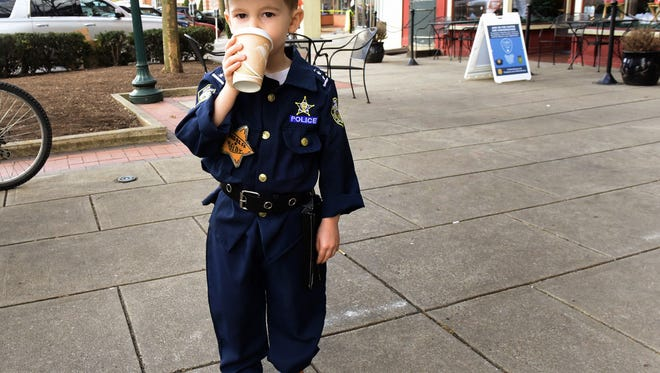 """Three year-old Kelby Elmer wears his crime fighter uniform in downtown Chambersburg after visiting C&C Coffee shop Friday, March 11, 2016. The shop hosted a """"Coffee with a Cop"""" event for citizens to meet and greet the officers who patrol out streets."""