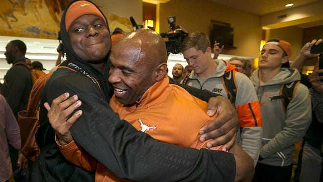 Texas linebacker Erik Fowler, left, gives coach Charlie Strong a hug after several players came to support and watch their coach address his coaching status on Monday.