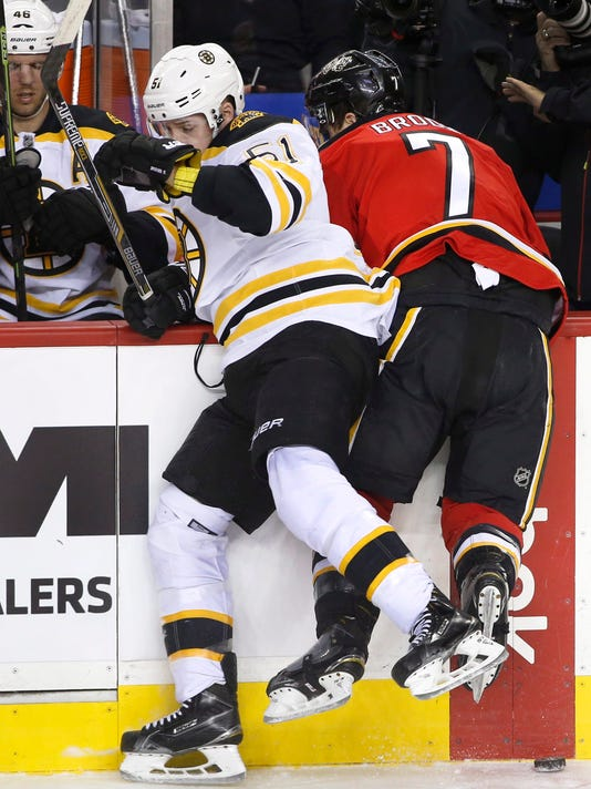 Boston Bruins' Ryan Spooner, left, hits Calgary Flames' TJ Brodie along the boards during the first period of an NHL hockey game Friday, Dec. 4, 2015, in Calgary, Alberta. (Larry MacDougal/The Canadian Press via AP)