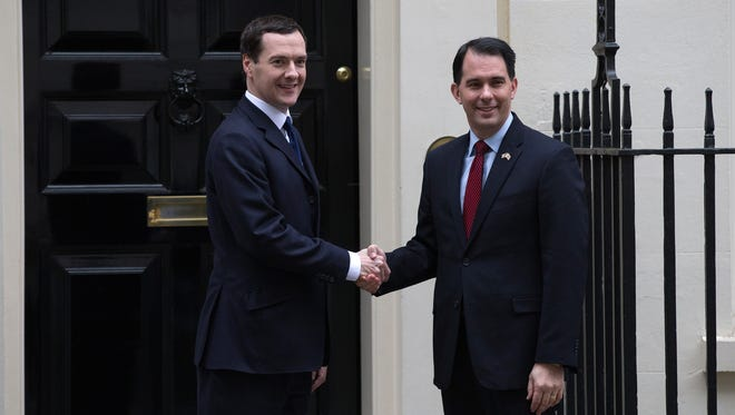 Wisconsin Gov. Scott Walker is greeted by Britain's Chancellor of the Exchequer George Osborne outside 11 Downing Street, the chancellor's official residence, in London on Wednesday.