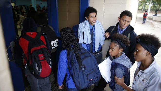 "Sophomore Deonte Ogltree, left, and Junior D.J. Phillips hold the lunch room door open for fellow students on ""Gentlemen's Day"" at Rickards High School."