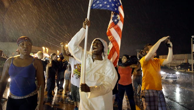 In this Aug. 9, 2015, file photograph, protesters march in the rain in Ferguson, Mo., in response to Michael Brown being shot and killed by Ferguson Police Officer Darren Wilson.