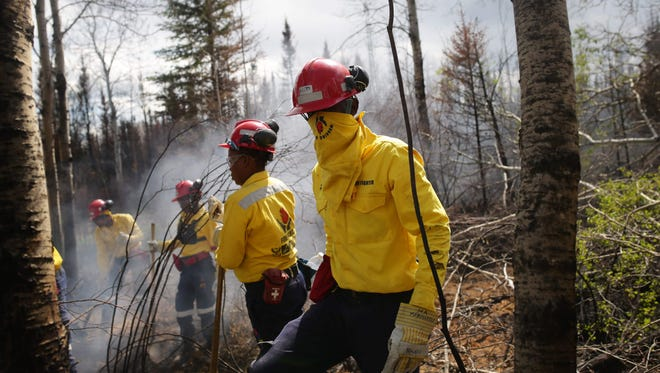 "Firefighters work to uproot a tree as they mop-up hot spots in an area close to Anzac, outside of Fort McMurray, Alberta on June 2, 2016.  In early July, the fire was finally declared ""under control."""